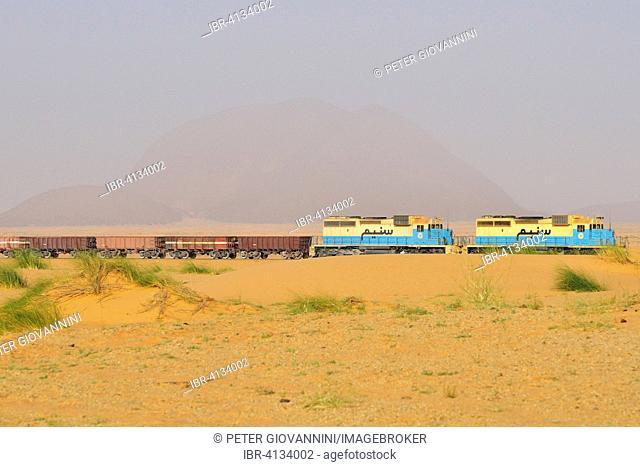 Railway through the desert for the transport of iron ore from M'Haoudat to Nouadhibou port, Monolit Ben Amira behind, Adrar region, Mauritania