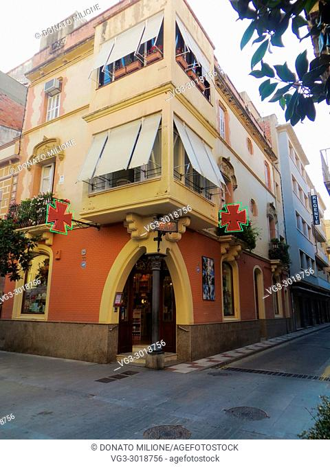 Sant Feliu de Guixols (Girona). A pharmacy on a corner of a building with a particular architecture. Catalonia, Catalunya, Spain, Europe