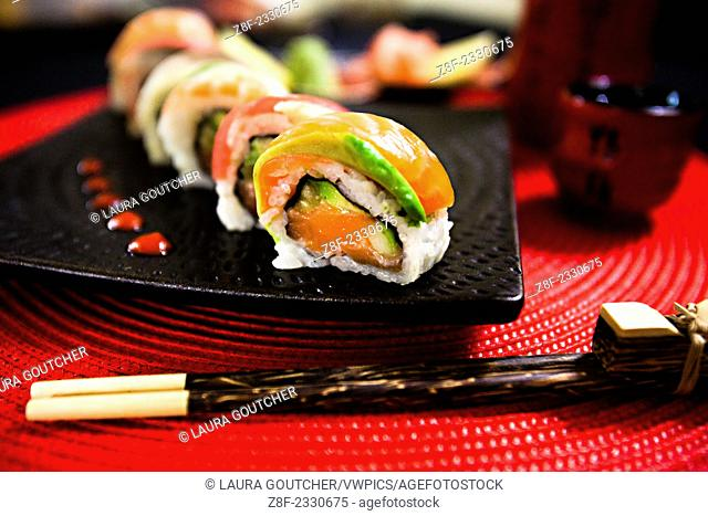 Rainbow sushi rolls are displayed with traditional chopsticks at a table