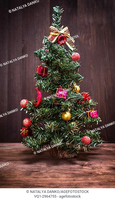 Artificial Christmas tree with toys on a brown wooden background