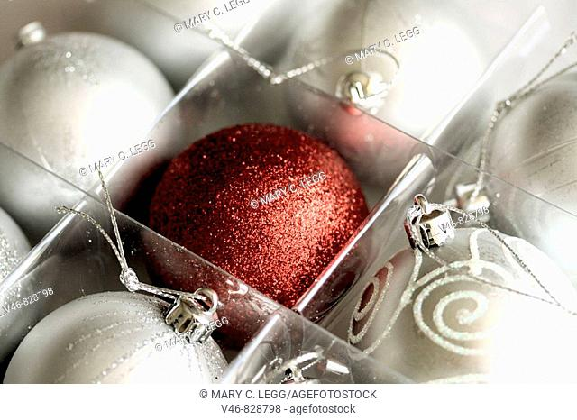 White Christmas balls and a red Christmas ball A box of eight satin white Christmas balls with a crimson ball in the center The red ball has a glitter surface