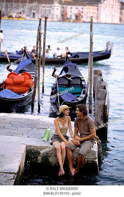 Caucasian sitting together by canal, Venice, Veneto, Italy