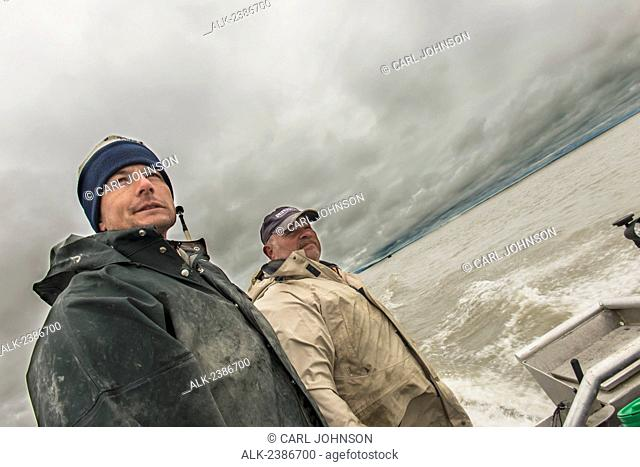 A skipper and crewman on a skiff look ahead to Coffee Point on the Nushagak River, where they will set gillnets for a commercial sockeye opener
