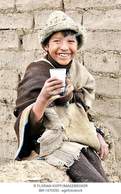 Shepherd boy, traditional dress, with a glass of milk, Bolivian Altiplano highlands, Departamento Oruro, Bolivia, South America