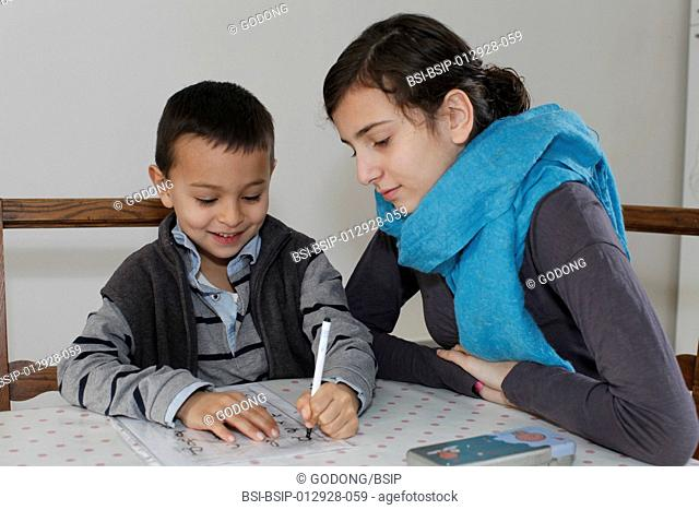 6-year-old boy writing with his sister