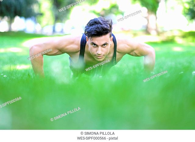 Young man doing push-ups in meadow