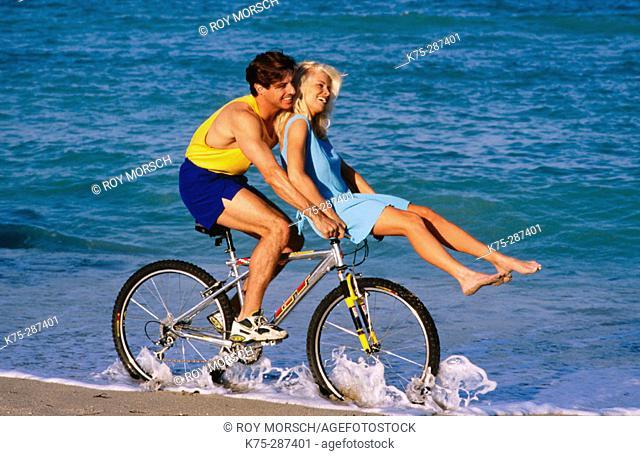 girl riding on her boyfriend's bike handlebars on the seashore