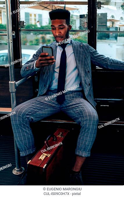 Businessman using smartphone on tram in city