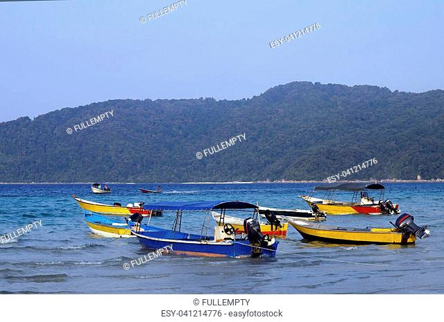 Sea and boats on sand beach in Penrhentian island (long beach) with view of Besar island in east Malaysia