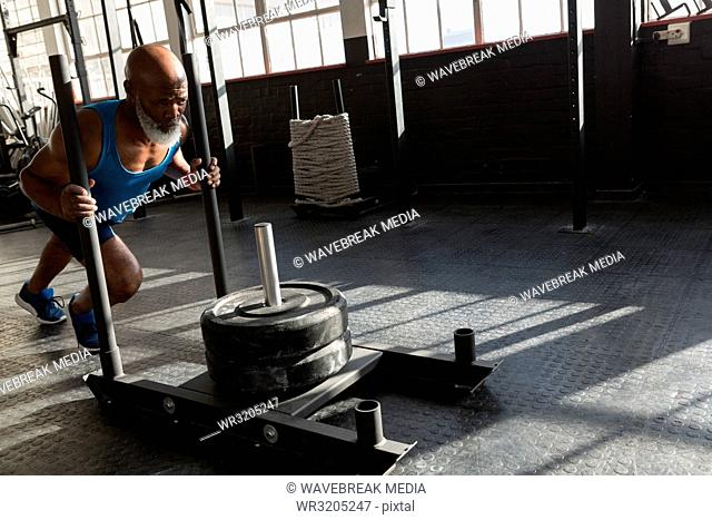 Senior man pushing weight sled in the fitness studio