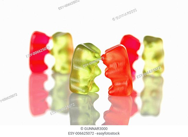 sweet gummy bears dancing on a party on white background