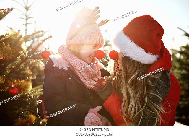 Girl and mother in christmas tree forest wearing red noses