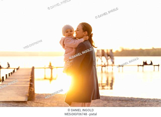Germany, Bavaria, Herrsching, mother carrying daughter at the lakeshore at sunset