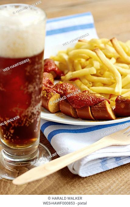 Vegan currywurst with french fries and a glass of top-fermented dark beer