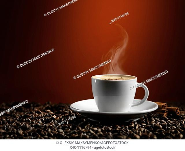Cup of coffe latte standing on coffee beans isolated on dark red background