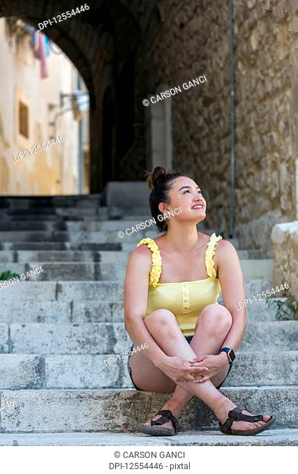 A young female tourist sits on stone steps looking up; Cefalu, Sicily, Italy