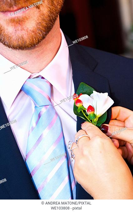 Groom being helped with the buttonhole flower on lapel