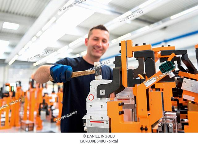 Factory worker hammering product in engineering factory