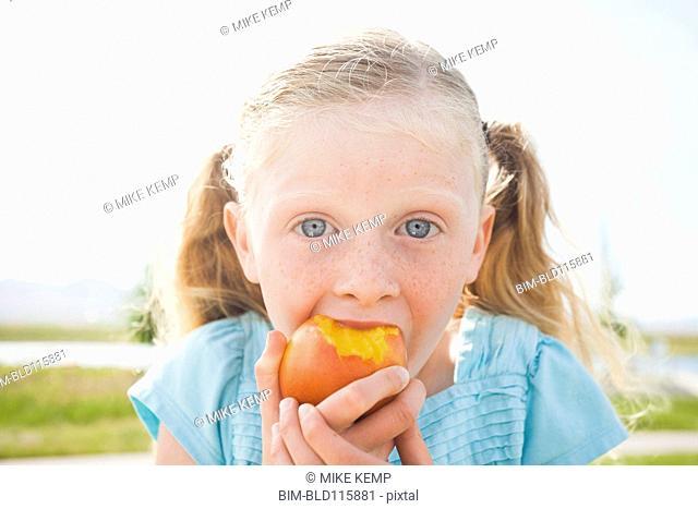 Caucasian girl eating fruit outdoors