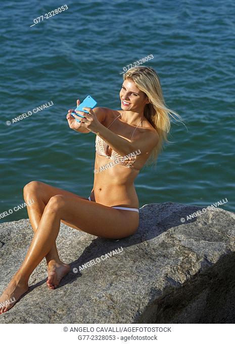 Young woman in bikini taking selfie on the beach. Miami Beach, Florida, USA