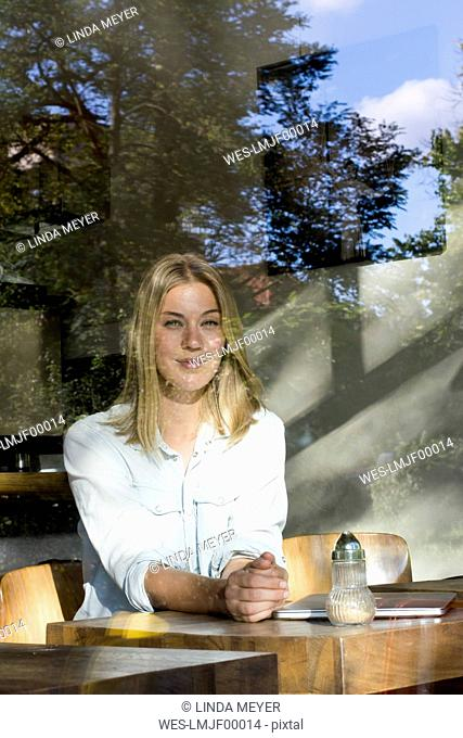 Portrait of blond woman in a cafe looking out of window