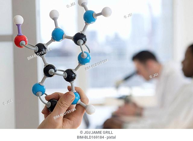 Close up of scientist holding molecular model in lab