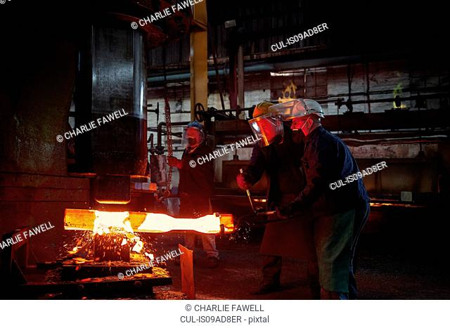 Forge workers pre form red hot steel billet into flight bar (mining component) on hammer
