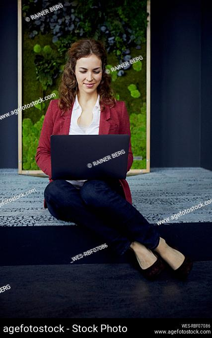 Smiling businesswoman sitting on the floor in green office using laptop
