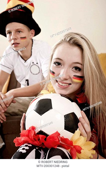 Teenage boy and girl with soccer ball in living room