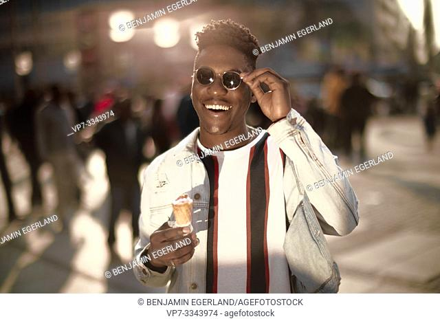 happy young African man with ice cream cone in city, in Munich, Germany
