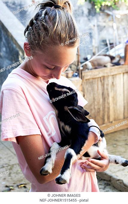 Teenage girl holding goat kid