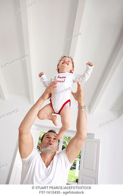 Father throwing his one year old son in the air