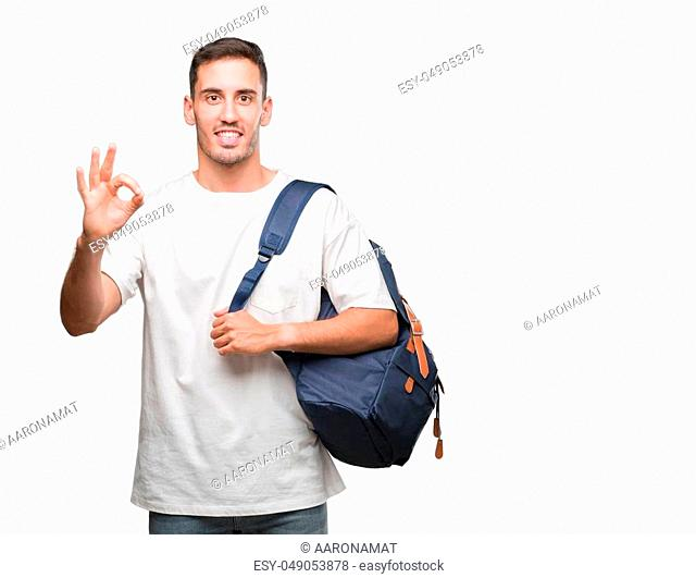 Handsome young man holding backpack doing ok sign with fingers, excellent symbol