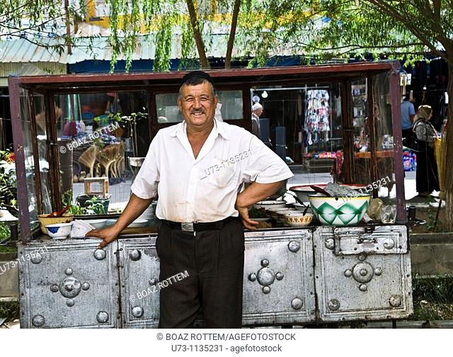 An Uighur man standing by his kebeb stall