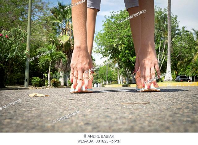 Mexico, Nayarit, hands and feet of teenage girl doing stretching exercise on a street