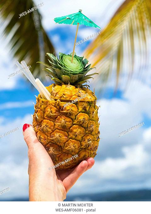 Woman's hand holding fresh pineapple with a straw