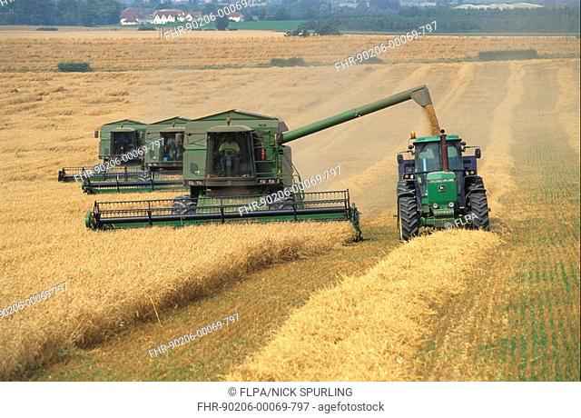 John Deere combine harvesters and tractor, harvesting wheat Triticum aesitivum Hertfordshire, Cambridgeshire border, England