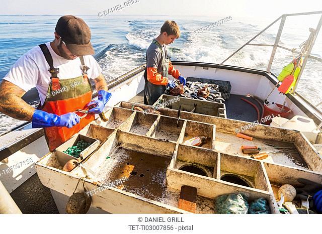 Two fishermen working on boat