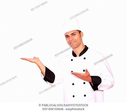 Portrait of a male chef with palms open to his right on isolated background - copyspace