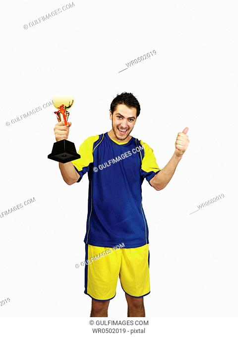 Young man showing thumbs up and holding trophy, smiling, portrait