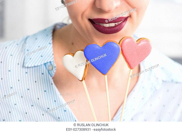 Closeup photo of the woman lips and gingerbread hearts on a stick, concept of love or valentines das