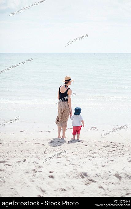 2 years old boy with his mother at the beach