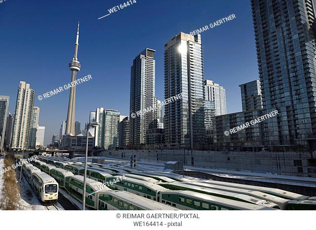 GO trains on railway tracks in downtown Toronto waiting for rush hour with CN tower and highrise condominium towers in winter