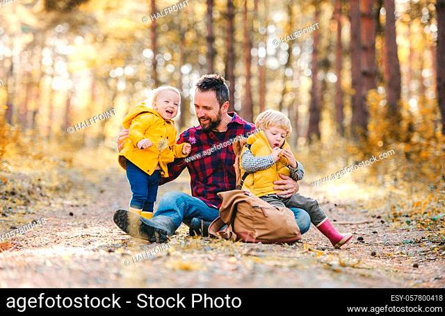 A mature father with toddler children sitting on the ground in an autumn forest, having fun