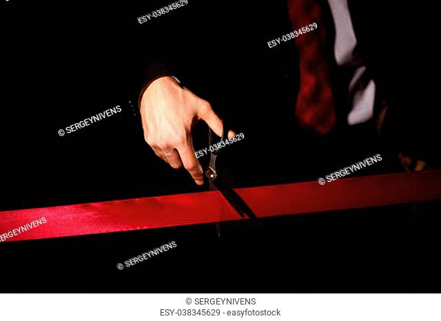 Hand of a businessman with scissors cuting a red ribbon