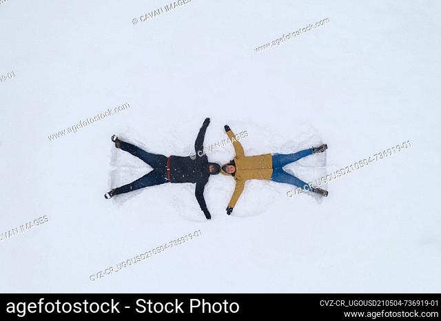 Young caucasian couple doing snow angels in a white snow field winter