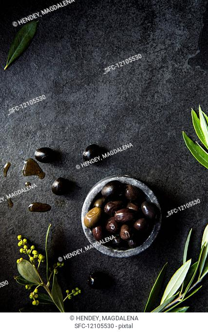 A bowl of olives with olive leaves