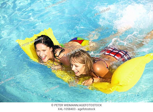 two women having fun with air mattress in the pool