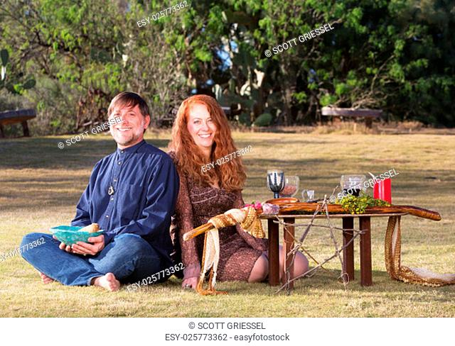 Happy pagan couple at altar with candles and goblets