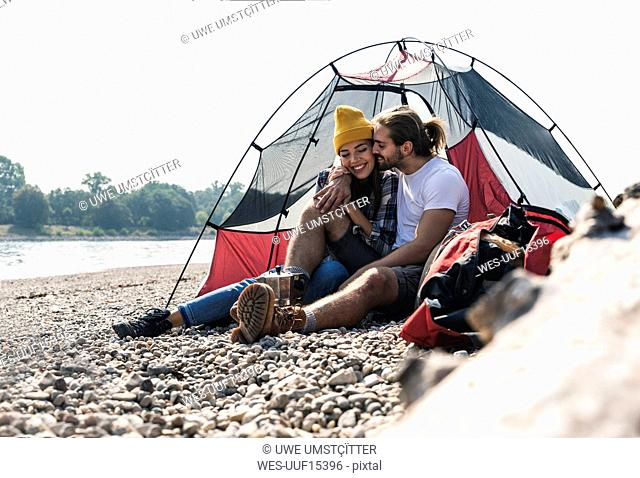 Happy young couple sitting at a tent at the riverside